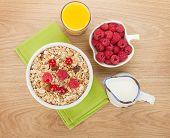 Healty breakfast with muesli, berries, milk and orange juice on wooden table