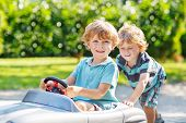 Two Happy Sibling Boys Playing With Toy Car