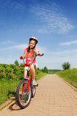 Teenage girl in red sitting on a bike