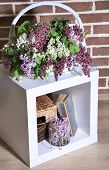 Beautiful lilac flowers in wicker basket, on stand, on color wall background