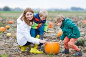 Mother And Two Little Sons Having Fun On Pumpkin Patch.