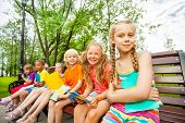Cute children with notebooks sit on bench
