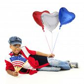 A young elementary girl reclining with stars and stripes in one hand and red, white and blue balloons in the other.  On a white background.