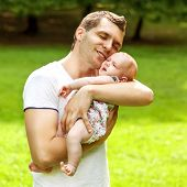 Dad And Newborn Daughter Playing In The Park In Love