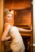 Young woman relaxing in a sauna, taking a break from her busy schedule, taking care of herself, enjo