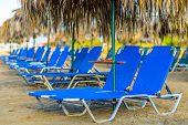 Beach Sunbeds With Straw Umbrellas