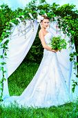 pic of wedding arch  - Beautiful elegant bride stands under the wedding arch - JPG