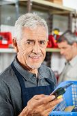 Portrait of confident senior salesman holding tool in hardware store