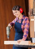 Portrait of happy female carpenter using drill machine on wood in workshop