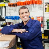 Portrait of mature worker leaning on tool package in hardware shop