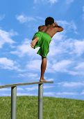 pic of aerialist  - A boy balancing on a beam in the park - JPG