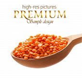 Red-orange lentil in a wooden spoon