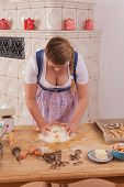 Young woman with deep cleavage kneads dough.