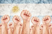 image of labourer  - Argentina Labour movement workers union strike concept with male fists raised in the air fighting for their rights Argentinian national flag in out of focus background - JPG