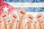 pic of labourer  - Cuba Labour movement workers union strike concept with male fists raised in the air fighting for their rights Cuban national flag in out of focus background - JPG