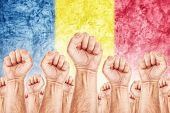 pic of labourer  - Romania Labour movement workers union strike concept with male fists raised in the air fighting for their rights Romanian national flag in out of focus background - JPG