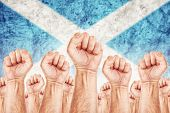 stock photo of labourer  - Scotland Labour movement workers union strike concept with male fists raised in the air fighting for their rights Scottish national flag in out of focus background - JPG