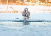 Winter swimming. Man to an ice-hole