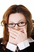stock photo of shame  - Businesswoman covering her mouth because of shame - JPG