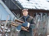 man holding an armful of firewood