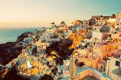 Oia town on Santorini island, Greece at sunset. Traditional and famous windmills on cliff over the Caldera, Aegean sea.