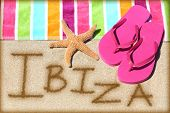Ibiza beach travel concept background. IBIZA written in sand with water next to beach towel, summer sandals and starfish. Summer and sun vacation holidays on Balearic Islands, Spain.