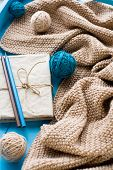 stock photo of blanket snow  - One old notebook in knitted cover lie next to the coil bright filaments and blanket knitted on blue background - JPG