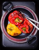 pic of pot roast  - Fresh roasted red and yellow peppers in pot selective focus overhead - JPG