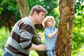 Cute Little Kid Boy Enjoying Climbing On Tree With Father, Outdoors.