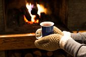 Holding Hot Coffee Or Tea By Fireplace