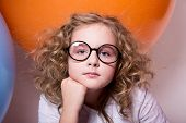 Beautiful, Smart Curly Teen Girl In Glasses On The Background Of Large Rubber Balls
