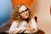 Portrait Of Curly Teen Girl In Glasses On The Background Of Large Rubber Balls