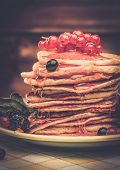 Tasty pancakes with maple syrup and fresh berries on a plate