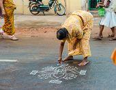Thanjavour, India - February 14: An Unidentified Woman Paints Ornaments Rice Flour On The Asphalt Ro