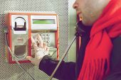 Man Pushing Buttons On Public Phone