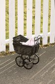 Vintage Stroller In Front Of White Fence