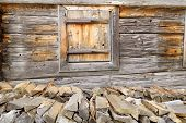 Firewood on the wooden wall of the barn