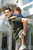 Happy father carrying his son on his back for a piggyback ride