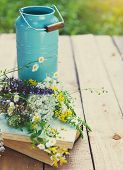 Flowers Near Watering Can With Old Books On A Rustic Wooden Table