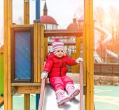 little cute girl playing at the playground in autumn