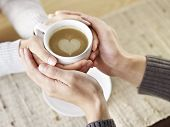 stock photo of lovers  - hands of young lovers holding a cup of coffee - JPG