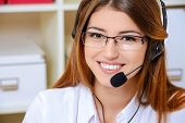 image of telephone operator  - Friendly smiling young woman surrort phone operator at her workplace in the office - JPG