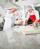 Smiling male chefs cooking ravioli pasta together at counter in commercial kitchen