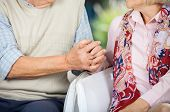 Midsection of senior couple holding hands while sitting on chairs at nursing home porch