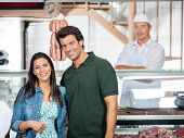 Portrait of happy mature couple standing in butcher shop