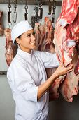Happy mid adult female butcher checking quality of meat hanging in butchery