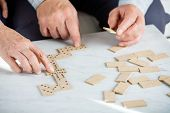 Copped image of senior couple playing dominoes at table in nursing home