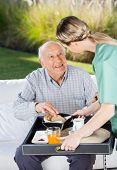 Female caretaker serving breakfast to senior man at nursing home