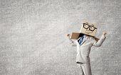 Businessman wearing carton box with drawn emotions on head