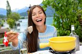 Swiss cheese fondue. Woman laughing showing and eating bread with melted local cheese. Traditional food from Switzerland. People having fun by lake in the Alps on travel in Europe.